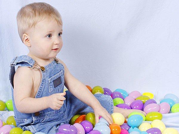 Niño jugando con huevos de Pascua. Tarjeta virtual para los niños