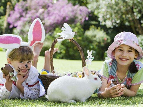 El conejo de Pascua y dos niñas. Tarjeta virtual para los niños