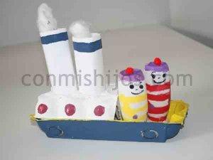 Una huevera convertida en barco de vapor y dos marineros de tubos de cartón.