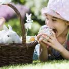 Niña comiendo un huevo de pascua. Tarjeta virtual para los niños